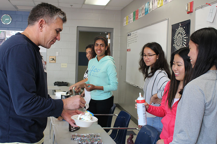 Mu Alpha Theta officers serve ice cream to math teacher Christopher Stanley in Kristine Visavachaipan's room on Nov 14. The officers scooped ice cream for the math teachers at their department meeting in honor of American Education Week.