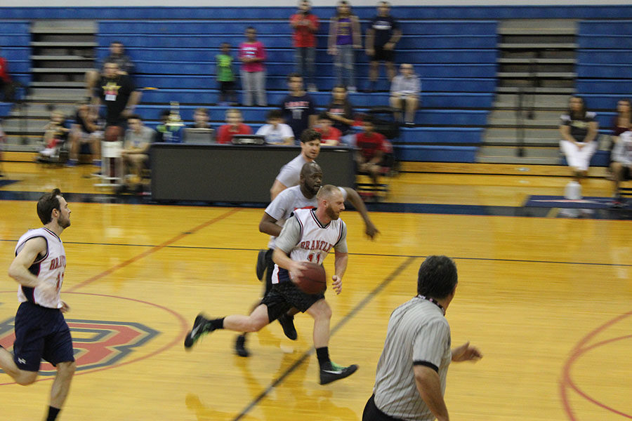 On Feb. 2, the Lake Brantley teachers' team advances the ball down the court of the main gym during the charity basketball game. While the men are not on any professional basketball teams, they still used teamwork and excellent shooting to play well.