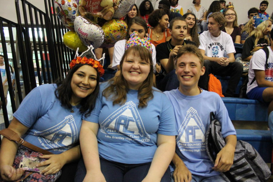 Seniors Andrea Romero and Ryleigh Hanners Graber sit with junior Corey Bleakley in the main gym as they wait for the pep rally to begin on Friday, August 23. Many seniors chose to wear their crowns the day of the pep rally too, showing senior school spirit.