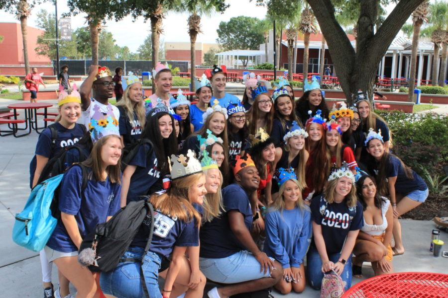 A group of seniors sporting their crowns gathers around the Darwin Boothe tree right after third period on Friday, August 16 for a picture. Senior crowns are a tradition at many high schools where seniors acquire crowns from Burger King and decorate them in their own unique way.