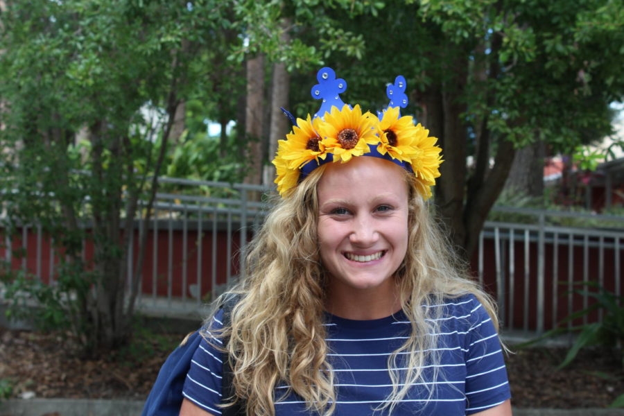 Senior Jennifer Simon smiles with her sunflower themed crown by the rocks on Friday, August 16. Sunflowers are a popular trend this year, as many display them on phone cases, Hydro Flasks, and now senior crowns.