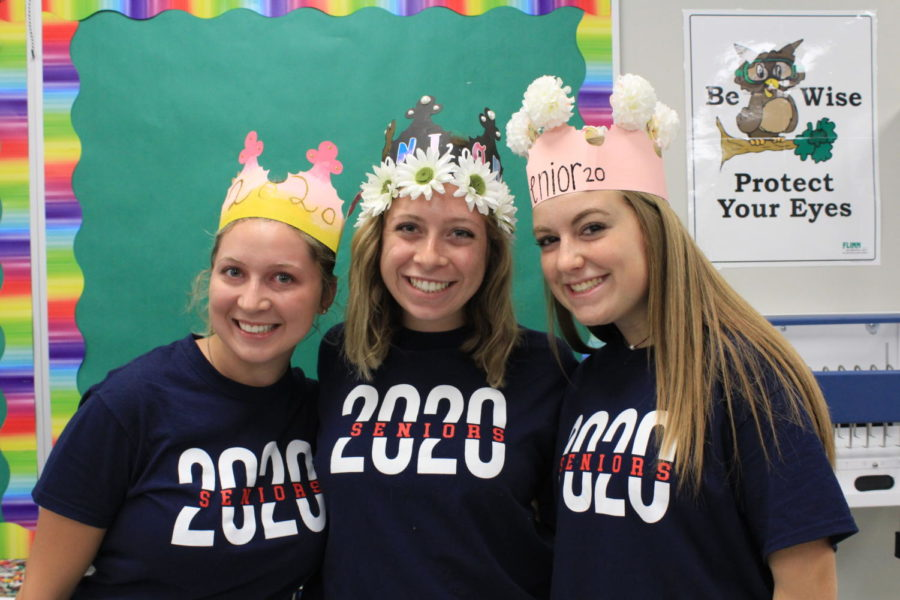 Holly Saca, Jacqui Gerber, and Ella Colley show off their colorful crowns during Lauren D'Ambrosio's AP Research class in room 5-018. Many seniors chose to decorate their crowns with artificial flowers from craft stores.
