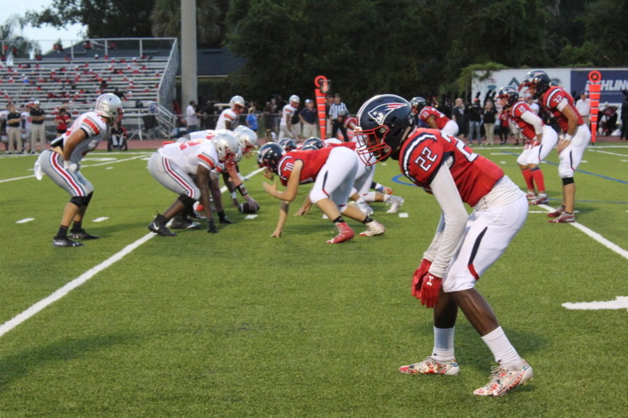 The football team lines up with Lake Mary High School at the line of scrimmage on Friday, Sept. 13. They prepared to play defense in the upcoming play.