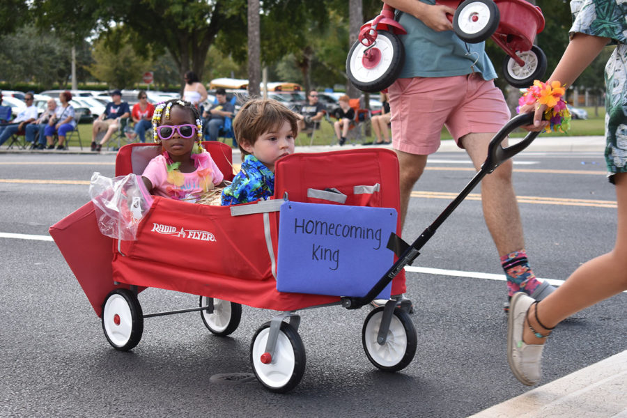 Two Little Patriots ride in a red wagon in the homecoming parade on Thursday, October 10. The Little Patriots always participate in the parade with their early childhood development helpers.