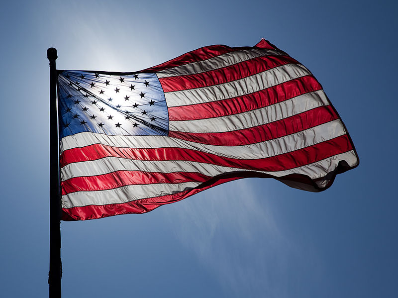 Flag of the United States of America, backlit, on a windy day.