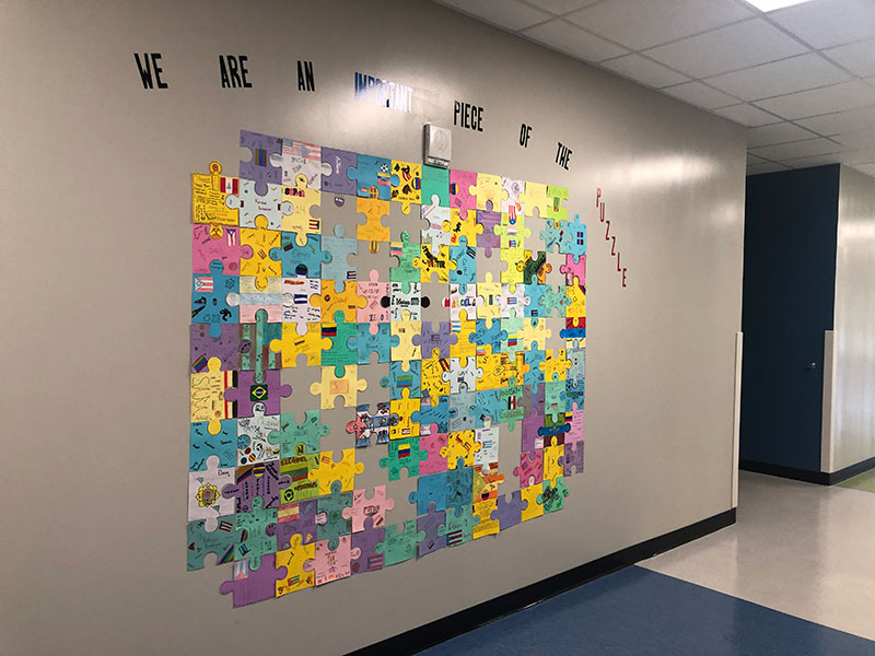 The wall outside of the ESL classes in Building 5 display a puzzle made up of pieces created by students in the ESOL program on August 30.