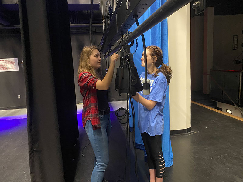 Junior Angelina Jonkaitis and sophomore Brooke Holland finish up moving a light. The lights were arranged five to a line in order to get the zones correct on the lightboard.