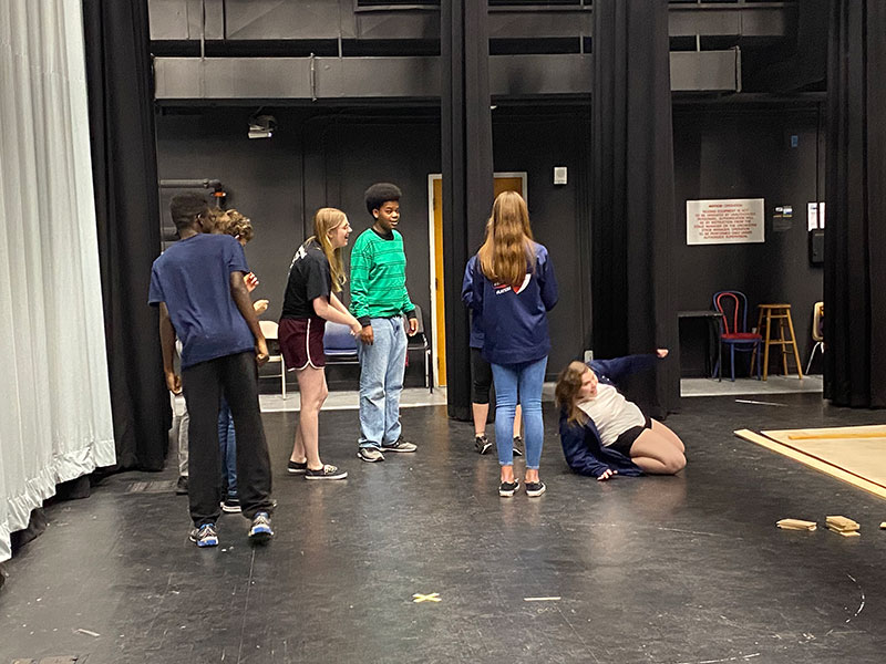 Troupe members cool off with a fun game of limbo while waiting for something to do. Work days can often be slow, but the end product of the set is very rewarding.
