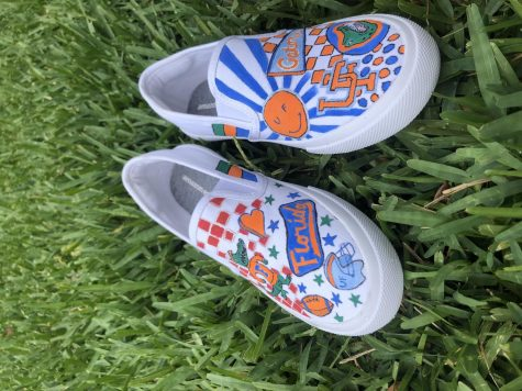 Senior Anna Wesley redesigned these white slip-on shoes to be perfect for gator game days. First, the designs were sketched out using pencil and then were filled in using acrylic paint mixed with fabric softener.