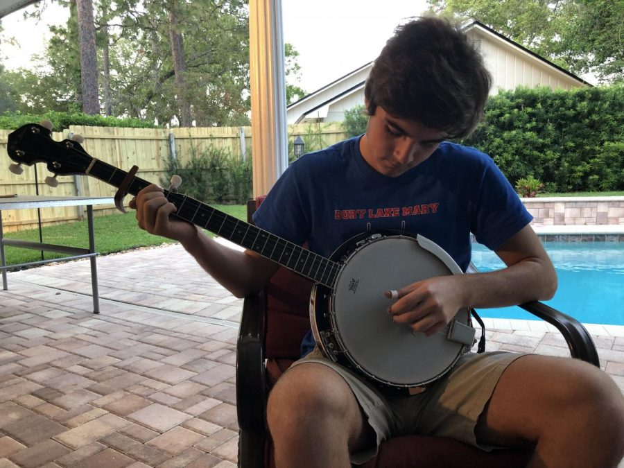 Senior Carson Cashion plays the banjo on his back porch on Tuesday, Apr. 7. Playing banjo is something he does not only to keep himself occupied, but to entertain both himself and his family during the quarantine.