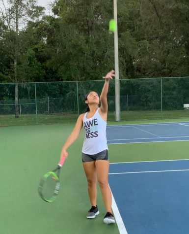 Junior Frans Louis Guinto takes a serve on the tennis court.