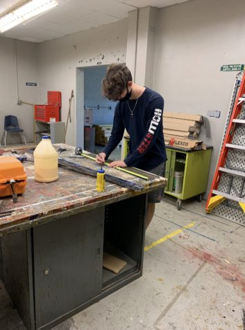 "Senior Justin Keyt marks off measurements before the woodshop class lays new flooring. ""This project was helpful because it introduced us to flooring,"" Keyt said. ""It was also special because most projects we do are for other parts of the campus, the new floors are in our shop."""