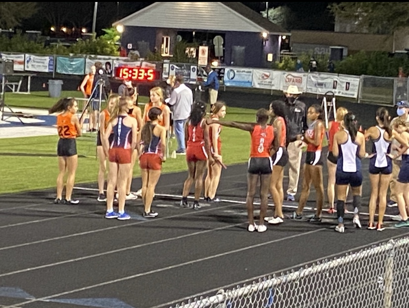 The Girls Track and Field team getting ready for the four by four. It is a relay where they each go around the track one time and pass the baton.