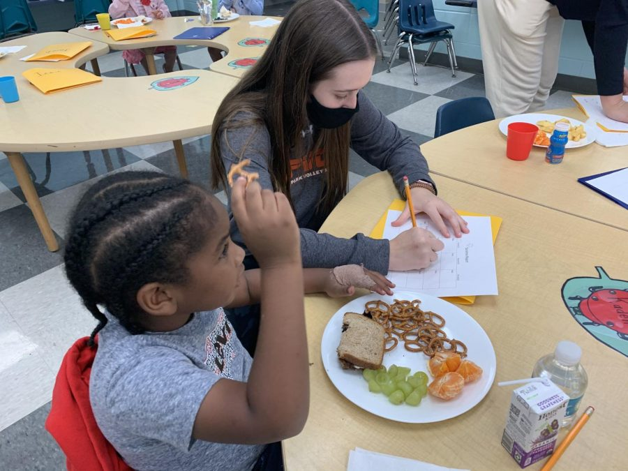 """After the children are seated at their appropriate spots for lunch, the high school student-teachers go around to each of their assigned preschoolers to fill out a form regarding their day """"We have a Sunshine Report where we have to ask them about their day and what they have been doing,"""" sophomore student-teacher Mayson Cooney said. """"We also fill out a lunch form where we record what they are eating and how much of it. It's important for their parents, so that their parents know what they did during the day, how much of their lunch that they ate, and what they need to pack or not pack in the future."""""""