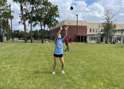 """Junior Rebecca Montanez attempts to catch a football at the Lunch Jam pep rally on Friday, Aug. 13. """"We're having so much fun and I love showing off my school spirit,"""" Montanez said. """"To get involved, I go to the sports games, join clubs and participate in events like this. It brings everybody together."""""""
